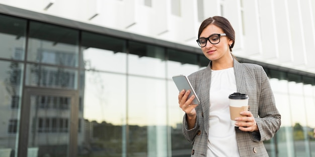 Donna di affari che mangia caffè all'aperto mentre guarda smartphone