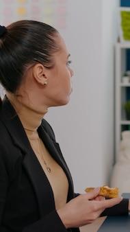 Donna d'affari che ha ordine di cibo per la consegna sulla scrivania durante l'ora di pranzo da asporto che lavora nell'ufficio della società commerciale. donna imprenditrice che mangia pranzo da asporto fetta di pizza digitando statistiche di gestione
