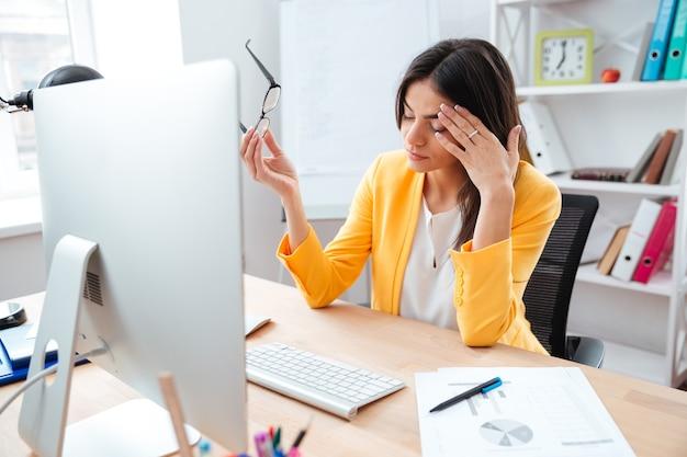 Donna d'affari che ha mal di testa in ufficio