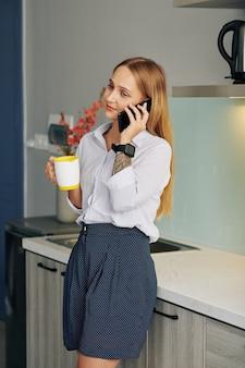 Donna di affari che mangia caffè del mattino
