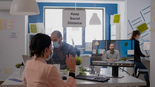 Donna d'affari che ha una riunione di videochiamata online, discutendo del progetto di comunicazione nel nuovo normale ufficio aziendale. la squadra che indossa maschere per il viso mantiene la distanza sociale durante la pandemia di coronavirus