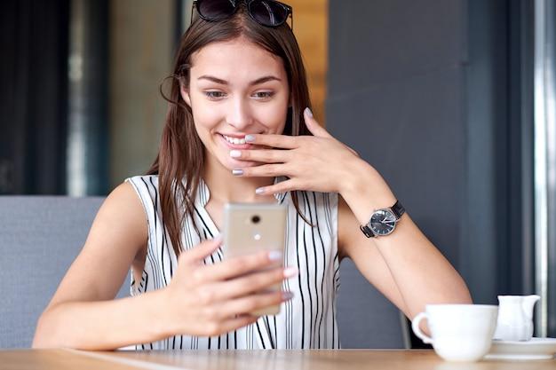 Donna di affari che ha sorpresa espressione dopo la ricezione del messaggio in caffetteria. effetto wow