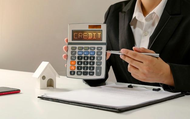 Donna d'affari che tiene una calcolatrice e punta una penna per accreditare il testo sul calcolatore del concetto di prestito delle pmi