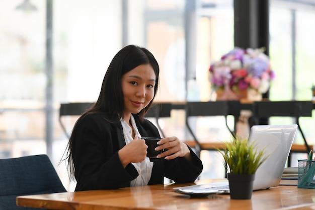 Imprenditrice tenendo la tazza di caffè e seduto davanti al computer portatile in ufficio moderno