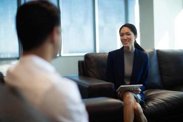 Donna di affari che tiene compressa digitale mentre discute con il collega maschio