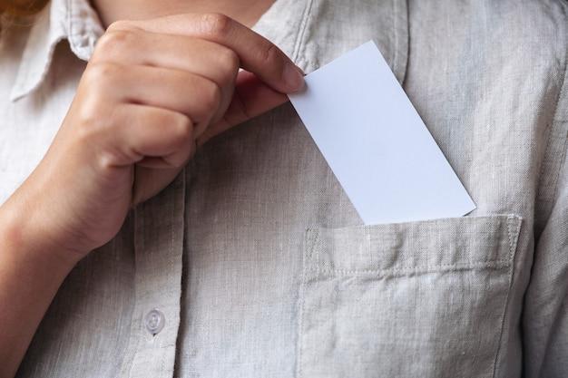 Imprenditrice tenendo e mettendo un biglietto da visita in bianco bianco nella tasca della camicia