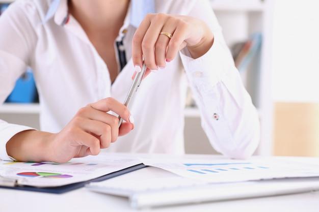 Donna di affari che tiene una penna d'argento in sua mano