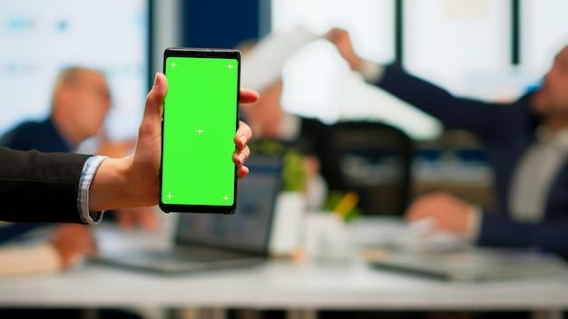 Donna di affari che tiene smartphone con schermo verde mentre diversi team lavorano sullo sfondo, uomini d'affari che analizzano le statistiche finanziarie, progetto di pianificazione multietnica di collaboratori sul display chroma key
