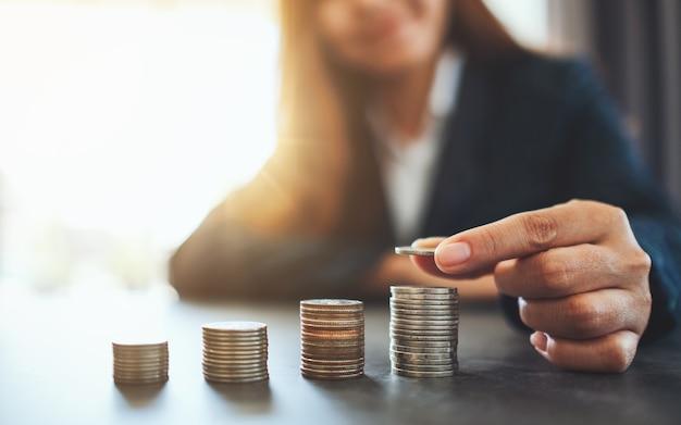 Imprenditrice tenendo e impilando le monete sul tavolo