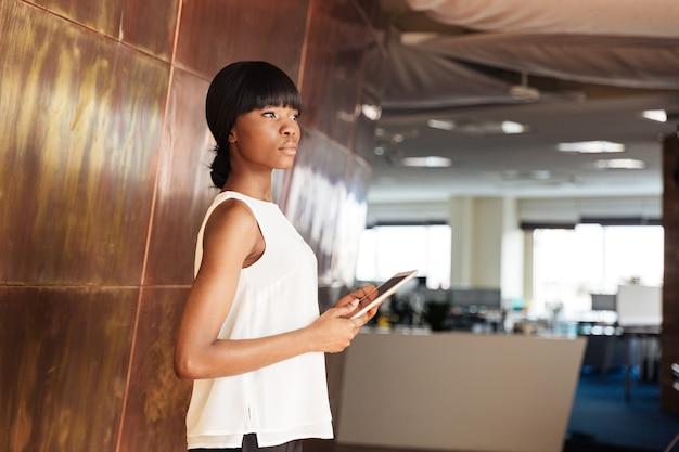 Donna di affari che tiene il computer tablet in ufficio e distoglie lo sguardo