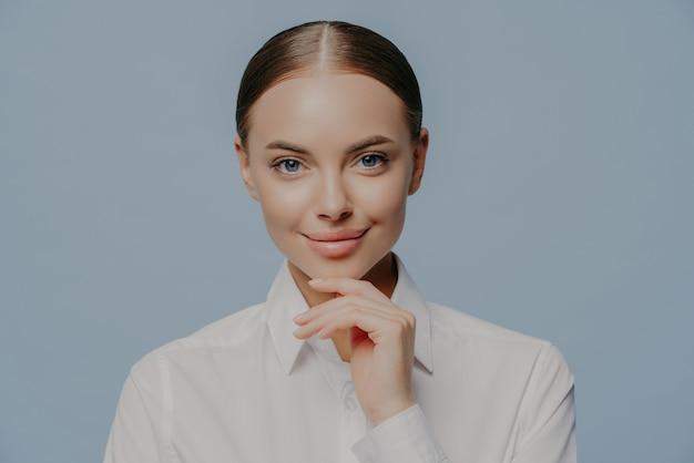La donna di affari tiene il mento, indossa una camicia bianca elegante, ha la pelle sana e il trucco naturale sul blu