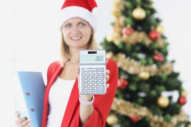 La donna d'affari tiene in mano la calcolatrice con i numeri sullo sfondo dell'albero del nuovo anno che riassume