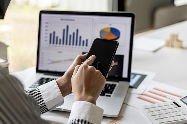 Una donna d'affari tiene in mano uno smartphone e lo utilizza, utilizza uno smartphone per inviare messaggi di testo a un partner aziendale sui rendiconti finanziari. concetto di utilizzo della tecnologia nella comunicazione.