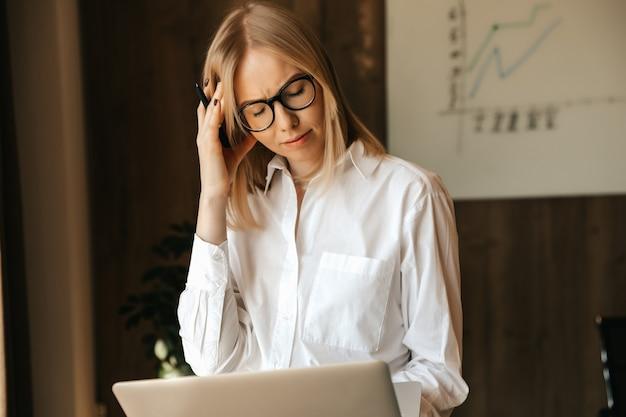 La donna d'affari è carica di lavoro e ha mal di testa lavorando al computer, stress sul posto di lavoro.
