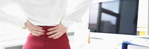 La donna d'affari è in piedi accanto alla sua scrivania e sente dolore nei suoi problemi alla colonna vertebrale mentre