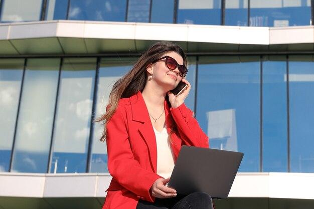 Una donna d'affari in giacca lavora con un laptop e chiama il telefono per strada