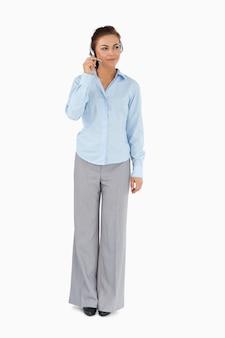 Donna di affari che ascolta il visitatore con la cuffia avricolare sopra