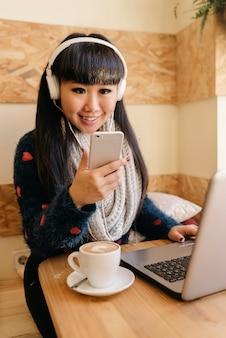 Musica d'ascolto della donna di affari nella caffetteria. concetto di affari