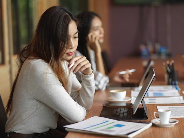 Imprenditrice guardando il rapporto finanziario sulla scrivania con forniture per ufficio laptop e collega
