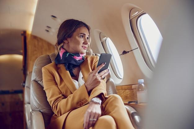 Imprenditrice guardando dalla finestra e utilizzare il telefono cellulare in aereo privato jet. aereo passeggeri moderno. la giovane donna europea indossa un abito formale. aviazione civile. concetto di viaggio aereo e affari