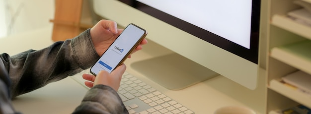 Imprenditrice alla ricerca su iphone con schermo linkedin