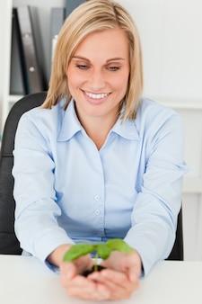 Donna di affari che esamina poca pianta verde