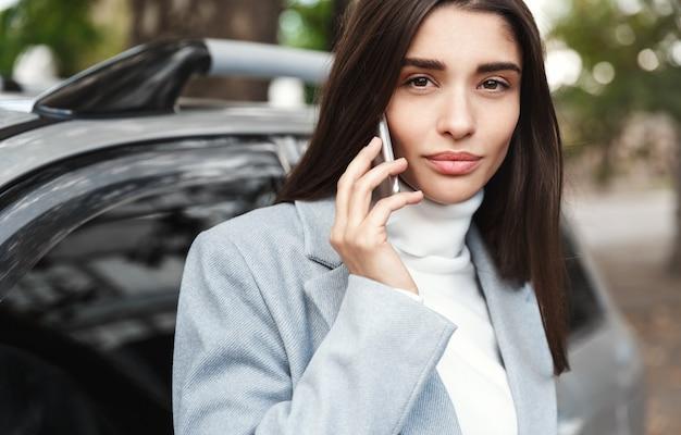 Donna di affari che fa telefonata vicino all'automobile.