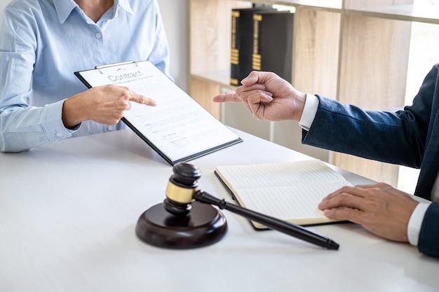 Donna d'affari e avvocati maschi che lavorano e discutono nello studio legale in ufficio