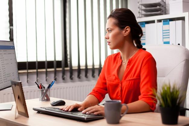 Manager di donna d'affari che lavora su competenze finanziarie professionali vestite di rosso datore di lavoro concentrato di successo con una carriera impegnata seduto alla scrivania in ufficio utilizzando un pc moderno.