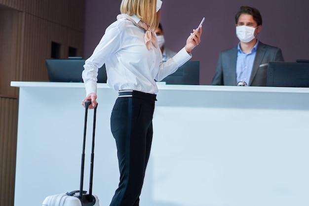 Donna d'affari in maschera alla reception di un hotel che fa il check-in