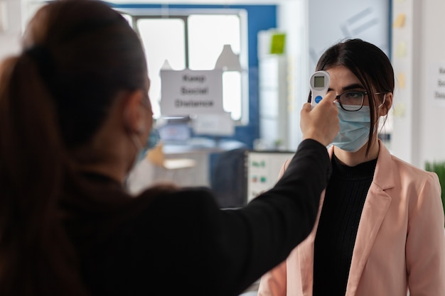 Donna d'affari che misura la temperatura utilizzando un termometro medico a infrarossi