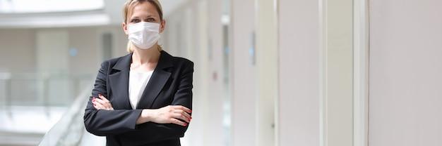 La donna d'affari in maschera protettiva medica sta con le braccia conserte nel corridoio dell'hotel