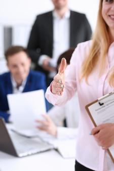 La donna di affari offre la mano da stringere come ciao in primo piano dell'ufficio