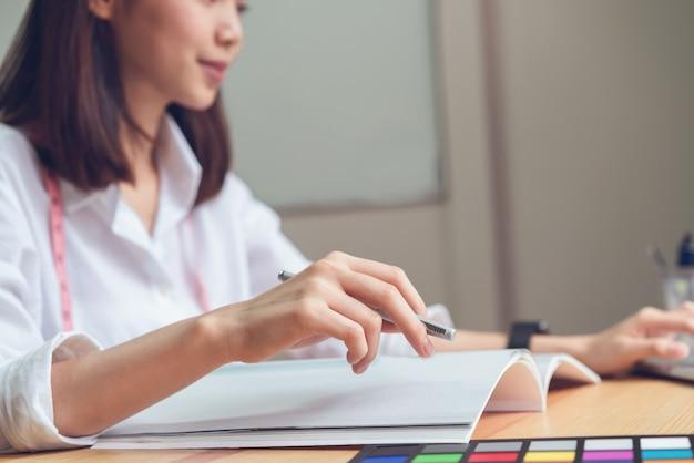 Imprenditrice in ufficio in camicia casual. usa il computer per il grafico.
