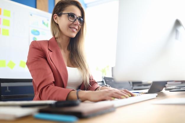Imprenditrice in ufficio si siede sul posto di lavoro al computer. concetto di consulente manager