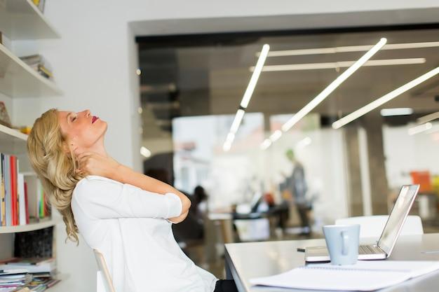 Donna di affari nell'ufficio che prende una rottura e che fa un esercizio del collo