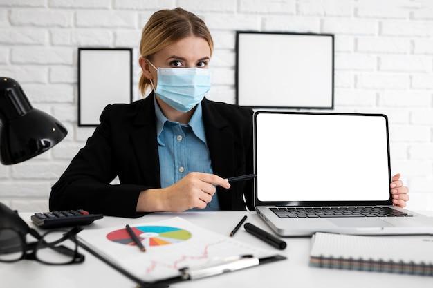 Imprenditrice in ufficio con mascherina medica e laptop