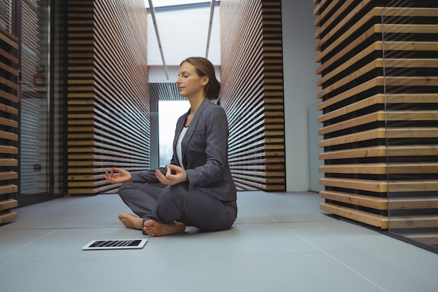 Donna di affari che esegue yoga nel corridoio