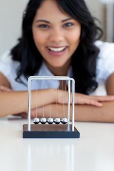 Donna di affari che gioca con le palle cinetiche