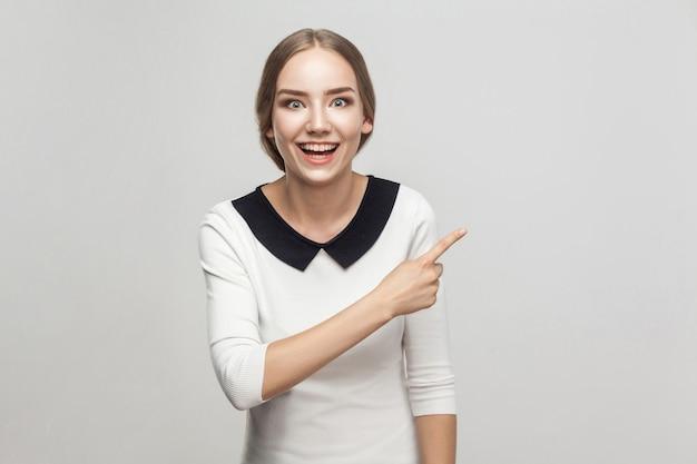 Donna d'affari che punta il dito contro lo spazio della copia, sorridente a trentadue denti e guardando la telecamera con il viso stupito. foto in studio, sfondo grigio