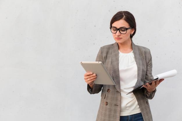 Donna di affari che propone all'aperto con il blocco note dell'annuncio della compressa
