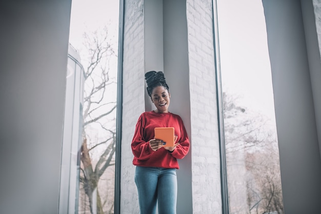 Imprenditrice. positiva donna afroamericana con un computer portatile in piedi vicino alla finestra