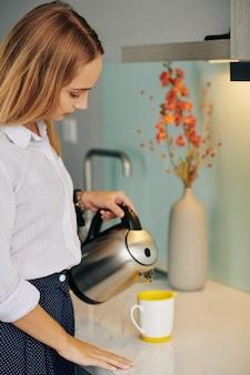 Donna di affari che versa acqua calda in tazza