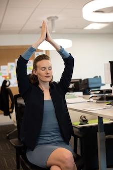 Imprenditrice a praticare yoga mentre è seduto su una sedia