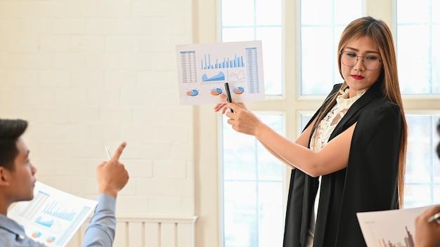 Presentazione della donna di affari con la carta millimetrata di finanza statica nella sala riunioni.