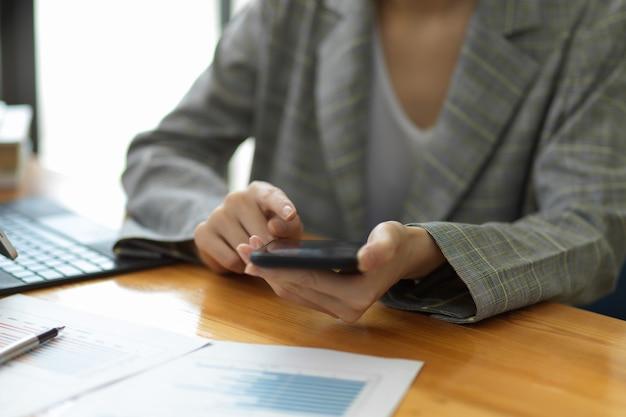 Responsabile professionale della donna di affari che lavora al telefono cellulare nell'area di lavoro dell'ufficio