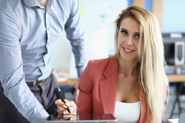 La donna di affari mette la firma elettronica sul primo piano della compressa