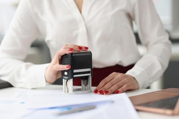 La donna d'affari mette il timbro sui documenti di credito alla scrivania per lo sviluppo di piccole e medie imprese