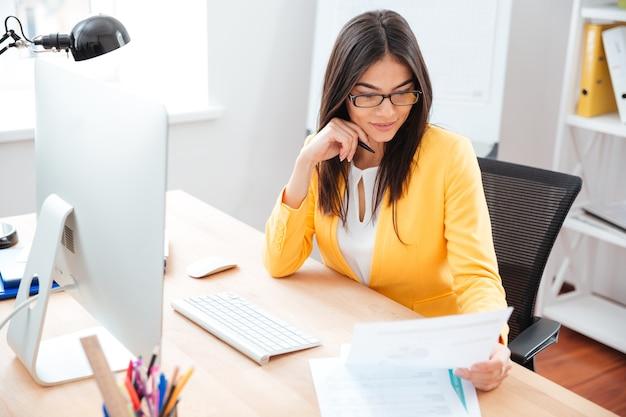 Donna d'affari che legge carta sul posto di lavoro in ufficio
