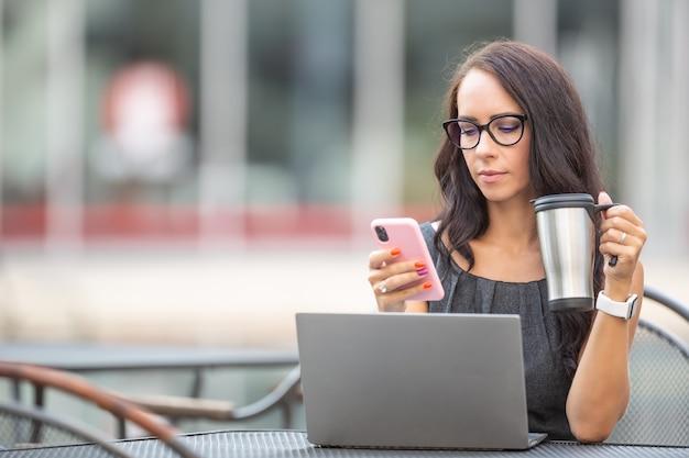 La donna di affari legge dal suo telefono mentre tiene il caffè da asporto davanti al pc all'aperto.